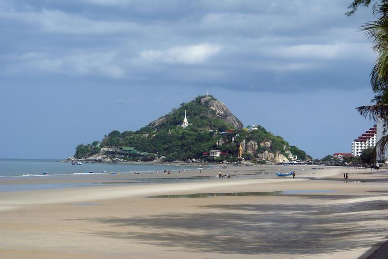 Strand i Hua Hin, Thailand med buddhisttempel på höjden i bakgrunden